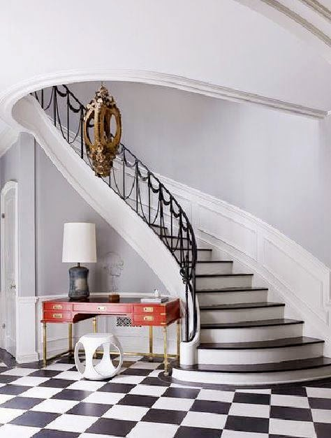 Curved Foyer Staircase With Black And White Tile Floor