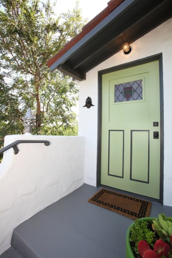 Green front door of a 1920's Spanish style home with black trim and a stain glass window