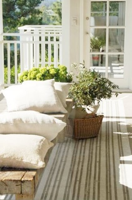 Outdoor patio with reclaimed wood bench, pillows and a striped rug