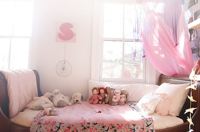 traditional wood sleigh bed with pink bedding in a girl's room with a pink canopy and white window