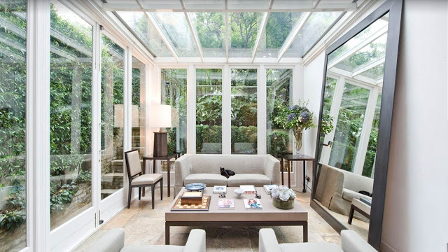 modern living room with glass walls and ceiling, a large floor mirror, neutral sofa, side tables and a coffee table