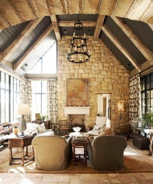 Rustic great rom in a tudor revival home with a stone fireplace, beamed ceilings, tile floor, a large area rug, large encasement windows with floor length patterned curtains, a wire chandelier, twin armchairs and an octagon side table