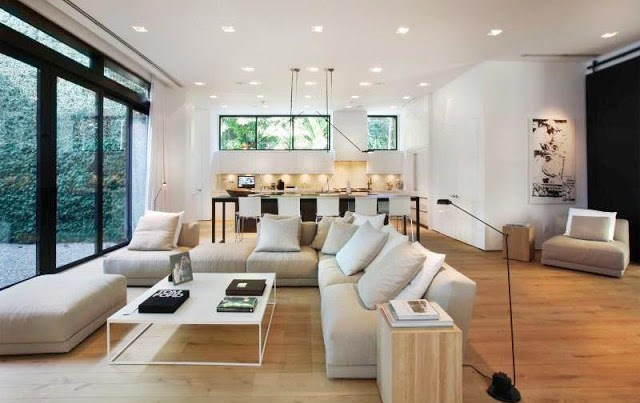 den with L-shaped sofa with neutral and white accent pillows, wood floors and a white metal coffee table