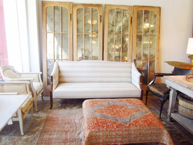Old mirrored doors are part of a living room display in Brenda Antin