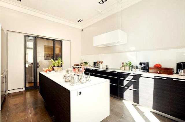 kitchen with wood fronts, no upper cabinets, white counter tops, island and large square tiles
