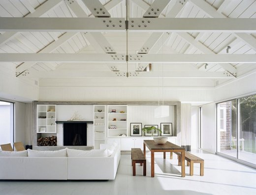 Family room with white sectional sofa, high ceiling with exposed beams, white bookcases a fireplace, picture windows and a long wood table with bench seating