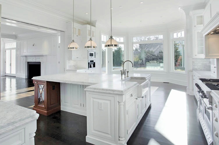 Alternative View Of The Kitchen With Hardwood Floors White Marble Counters Stainless Steel Appliances