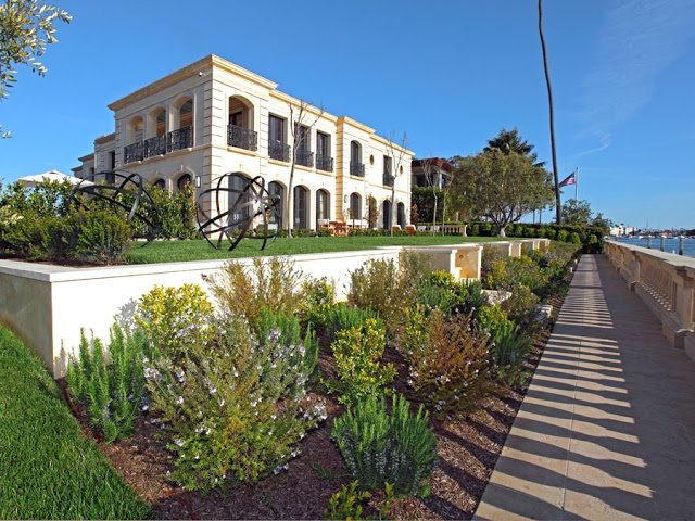 Exterior of french limestone mansion on harbor island in newport beach California with a lawn, backyard, an ocean view and two round sculptures