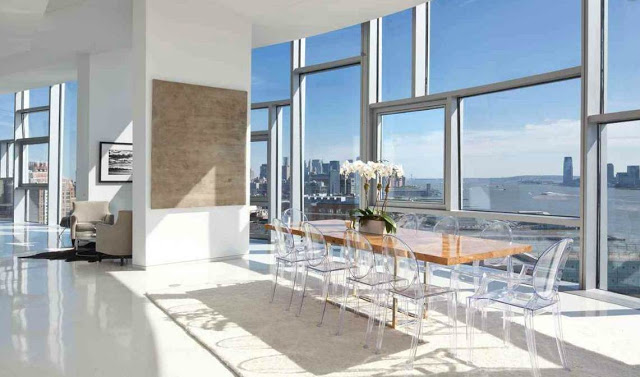 Dining room with Louis Ghost Chairs, wood table and huge windows with a great view of NYC