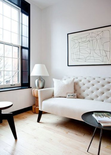 Den in an apartment with light wood floor, white tufted sofa with black legs and upholstered, an oversized wooden doubles as a side table and two black coffee tables