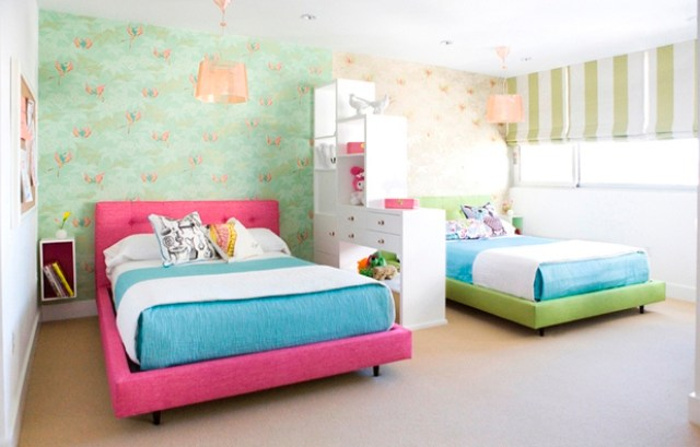 Girls bedroom with pink and green upholstered beds separated by a white drawer and shelf divider, each half of the room has the same wall paper in different color, the blinds are lime green striped