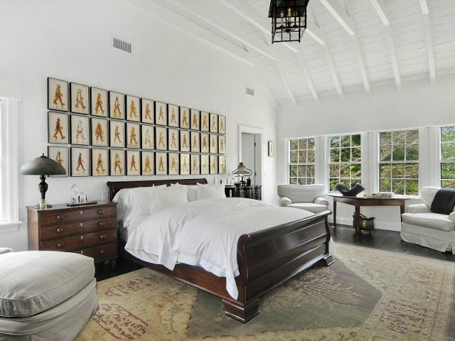 Bedroom in an East Hampton compound with a gallery wall, wood floor and lantern lamp