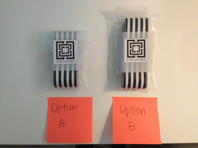 """Two black and white stripped ribbons folded neatly wrapped in plastic with COCOCOZY's logos on them on a white table. An orange post it note is in front of each stack with either """"Option A"""" or """"Option B"""" written on it"""