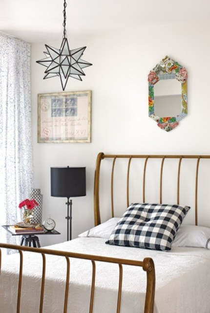 Bedroom with wire frame bed, gingham accent pillow, a small mirror above the metal headboard and a star pendant light