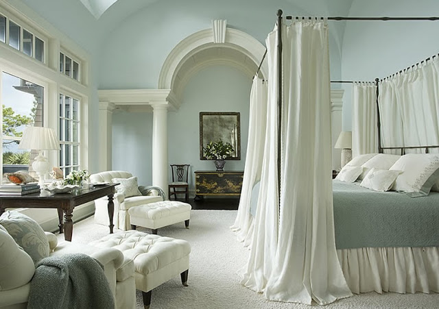 Blue bed room in a South Carolina estate with a canopy bed and white armchairs with matching ottomans