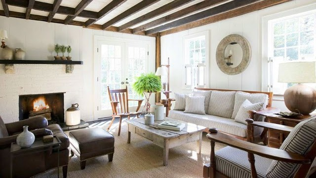 Living room with ticking stripe sofa chairs, exposed beams, a white fireplace, reclaimed wood coffee table, french doors with a sisal rug