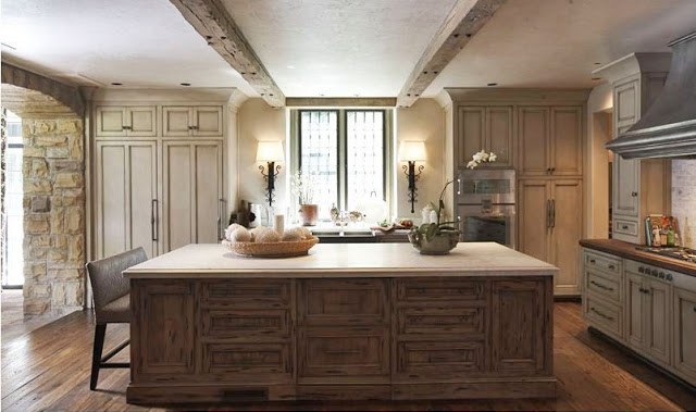 Large kitchen with a huge island with reclaimed wood cabinets and counter height bench seating. The rest of the kitchen has reclaimed wood cabinets, exposed beams and a wood floor
