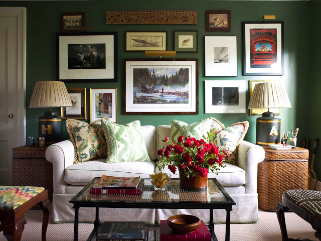 Green living room with a gallery wall, taupe sofa and woven baskets doubling as side tables