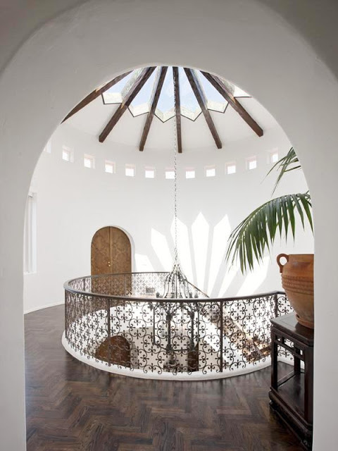 View from the second floor landing of the glass cathedral ceiling, Moorish ironwork railing and herringbone wood floors