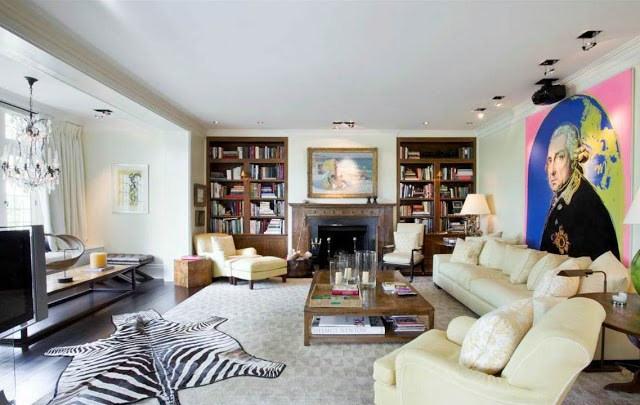 Family room in a mansion with zebra skin rug, wood floor, fireplace, built in bookshelves, white sofa and a large modern art portrait of George Washington