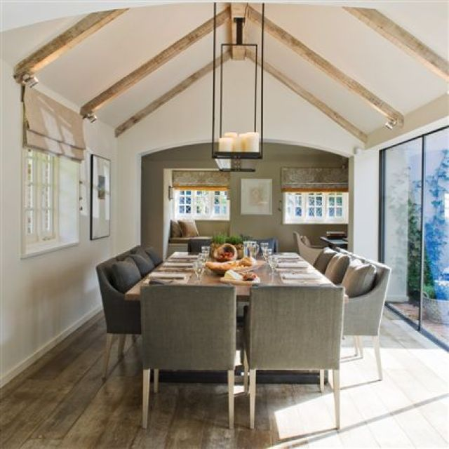 Dining room with glass wall sliding door, reclaimed wood floor, exposed beams, a chandelier and grey upholstered chairs
