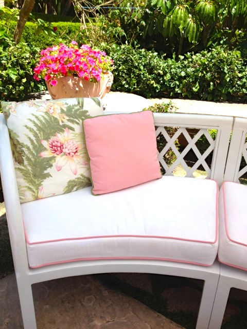 White curved sofa with pink pimping and decorative floral pillows