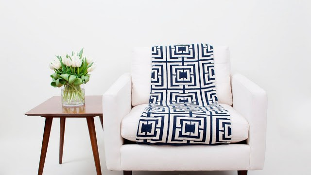 COCOCOZY Logo Throw placed straight down the middle of a white armchair next to a wooden side table with a glass vase full of tulips