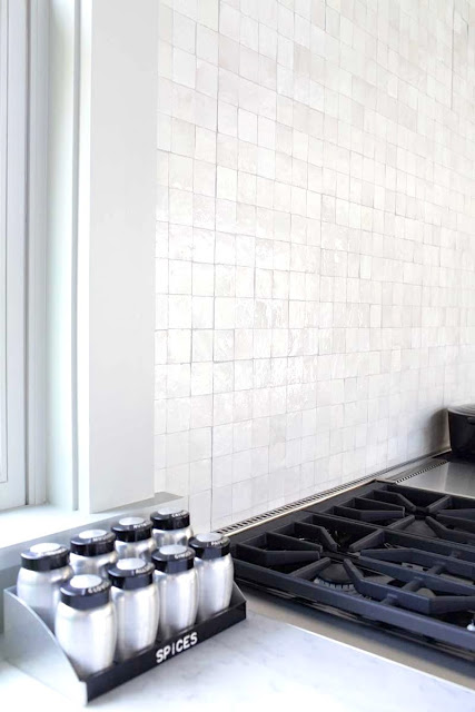 Mosaic tile backsplash behind stove and sink