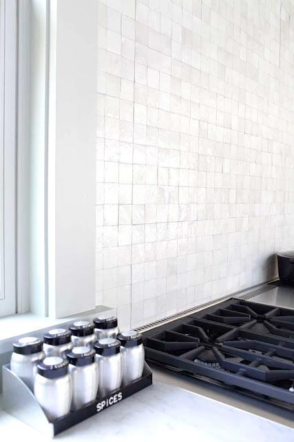 Mosaic tile backsplash behind stove and sink