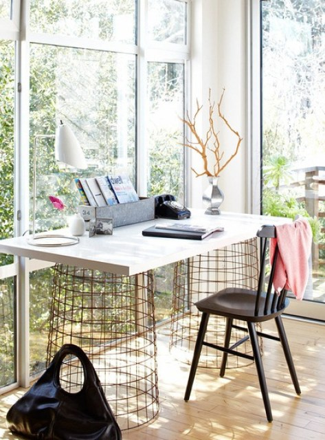 home office with large windows overlooking a backyard, wood floors and a desk with a white top with wire drums holding it up