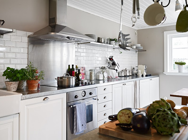 White kitchen in a Swedish cottage white subway tile backsplash stainless appliances marble counter tops white drawers and cabinets