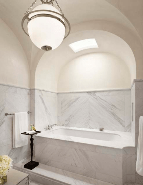 Marble bathroom with high curved ceiling by Michael Imber