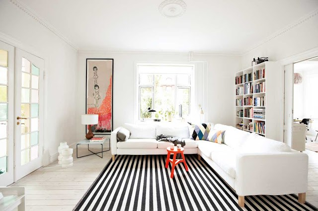 living room modern orange accents, black and white striped rug, white sectional sofa, white bookcase full of books and french doors
