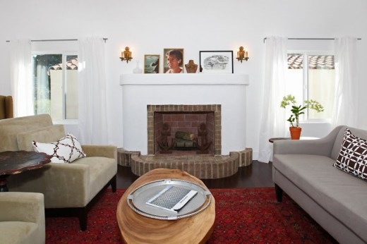 Living room in a Spanish Style home with Koa wood floor, wing back armchairs and a grey sofa with COCOCOZY decorative throws and pillows, red Moroccan rug and brick fireplace