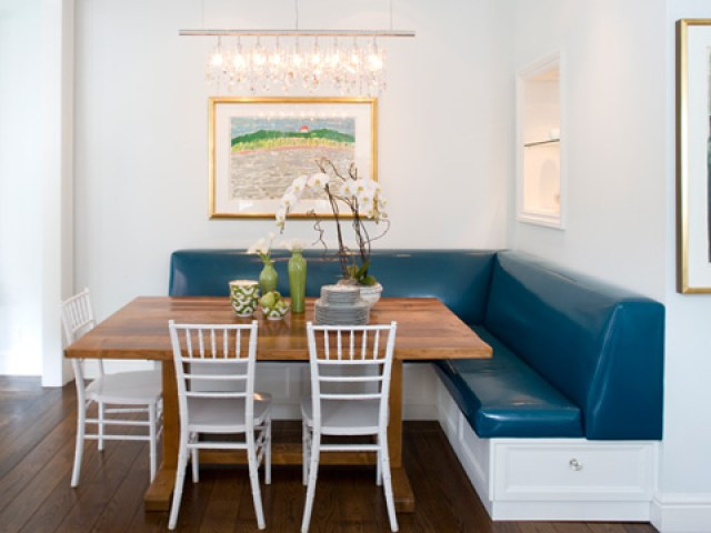 kendall wilkinson' breakfast nook with a large wooden table surrounded by white chairs and benches with blue leather coverings