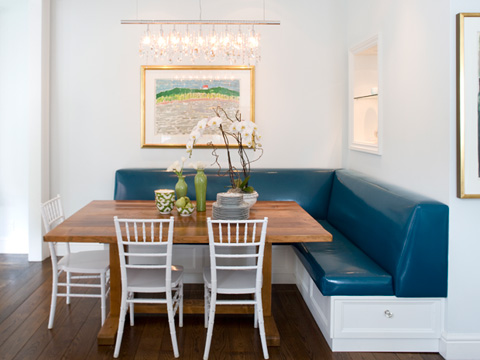 Luxury kendall wilkinson u breakfast nook with a large wooden table surrounded by white chairs and benches