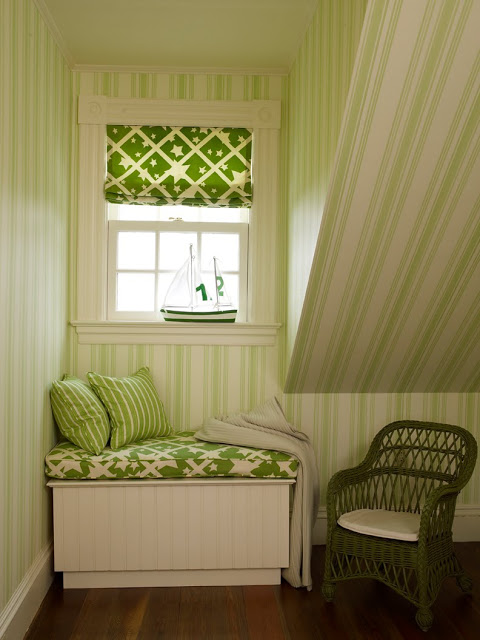 short window seat with green and white cushion, striped accent pillows and a slanted ceiling with green and white striped wall paper