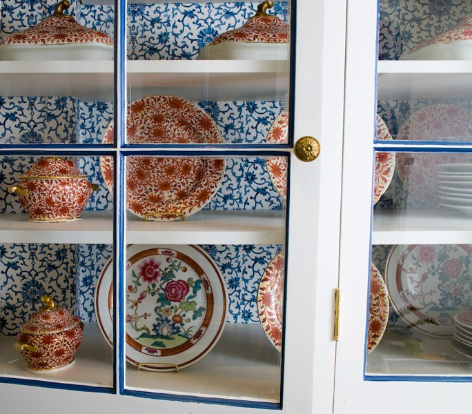 Glass Front Upper Kitchen Cabinets With Blue And White Wallpaper Inside The