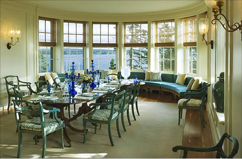 Dining room by Peter Pennoyer with bay windows with a view of the ocean, a long table surrounded by metal chairs and curved sectional sofa