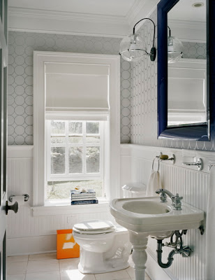 Bathroom by Ghislaine Vinas with wainscoting on the walls, grey wallpaper and a porcelain washstand and bright orange wastebasket