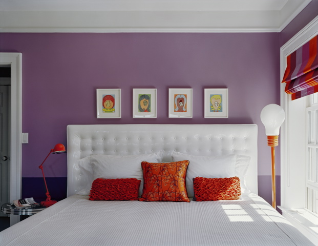 Purple bedroom by Ghislaine Vinas with a white tufted headboard with orange accent pillows and lamps