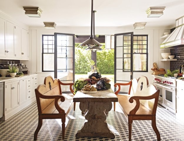Eat in kitchen by Steven Gambrel with outdoor benches surrounding a 19th Century oak table, pendant lights and a grey and white prism tile floor