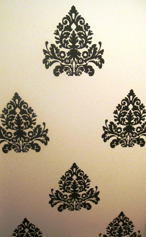 Close up of dark grey medallion brocade wall decals in the entryway of a nursery in a NYC loft