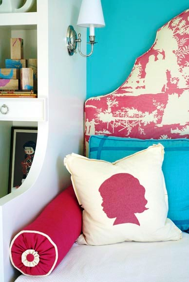 Bedroom with silhouette printed throw pillows match that match the pink and white toile upholstered headboard and turquoise pillows match the wall