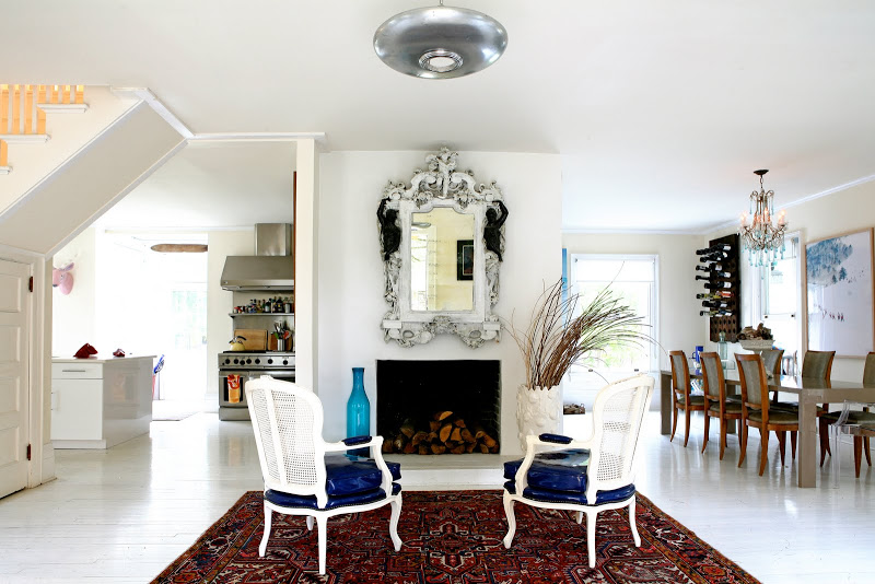 Formal living room by Robert and Cortney Novogratz with a Persian rug, white lacquer fauteuils in front of a fireplace with a large venetian glass mirror