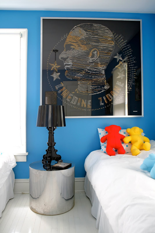 Blue room by Robert and Cortney Novogratz with a round silver side table, black lacquer lamp and a large black portrait