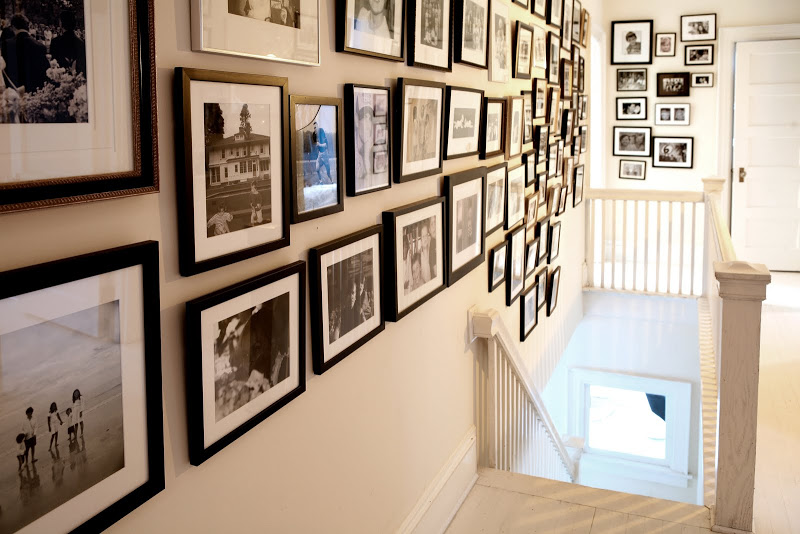 Stairwell lined with black and white photos and prints in Robert and Cortney Novogratz's home