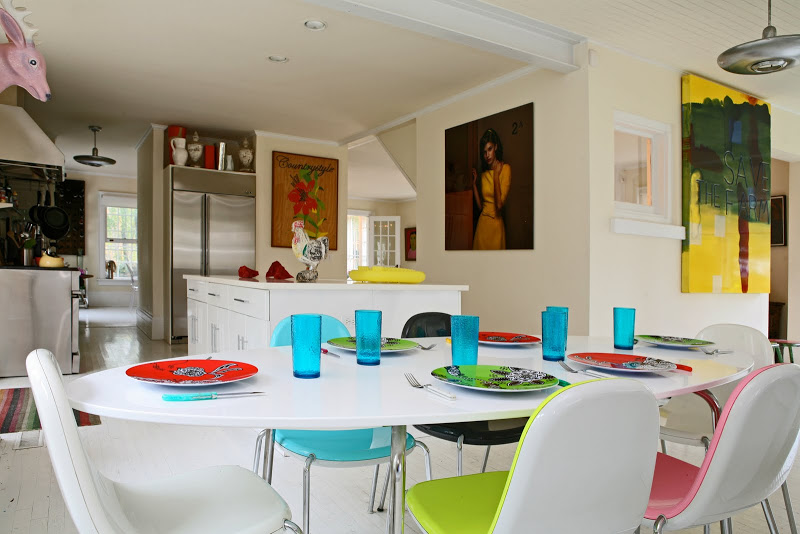 Casual dining room by Robert and Cortney Novogratz with large white oval dining table and colorful chairs, plates and glasses