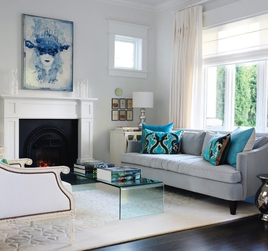 Modern meets traditional in a light airy living room with white fireplace and light blue sofa