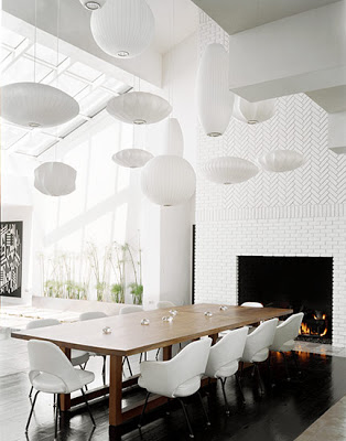 12 Nelson bubble suspension lights in different shapes and sizes hang over a modern dining room table with white Saarinen arm chairs and side chairs